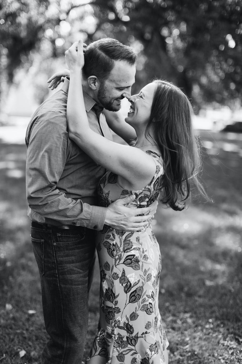 grayscale photography of smiling couple standing beside trees