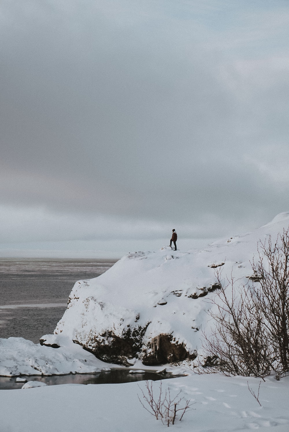 man standing on snow-covered mountain cliff facing ocean