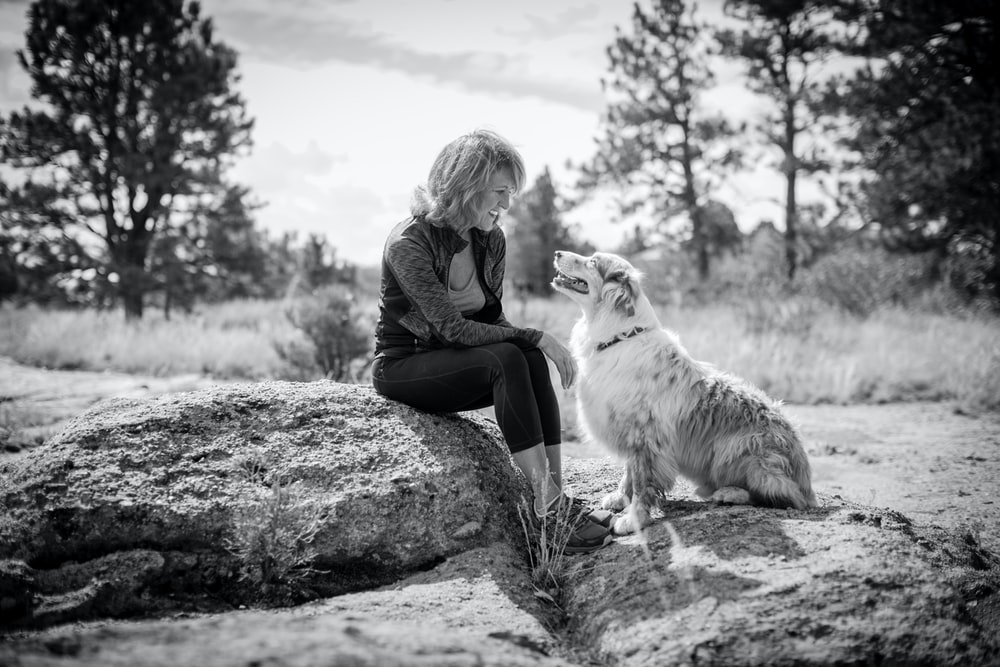 woman sitting on rock with dog