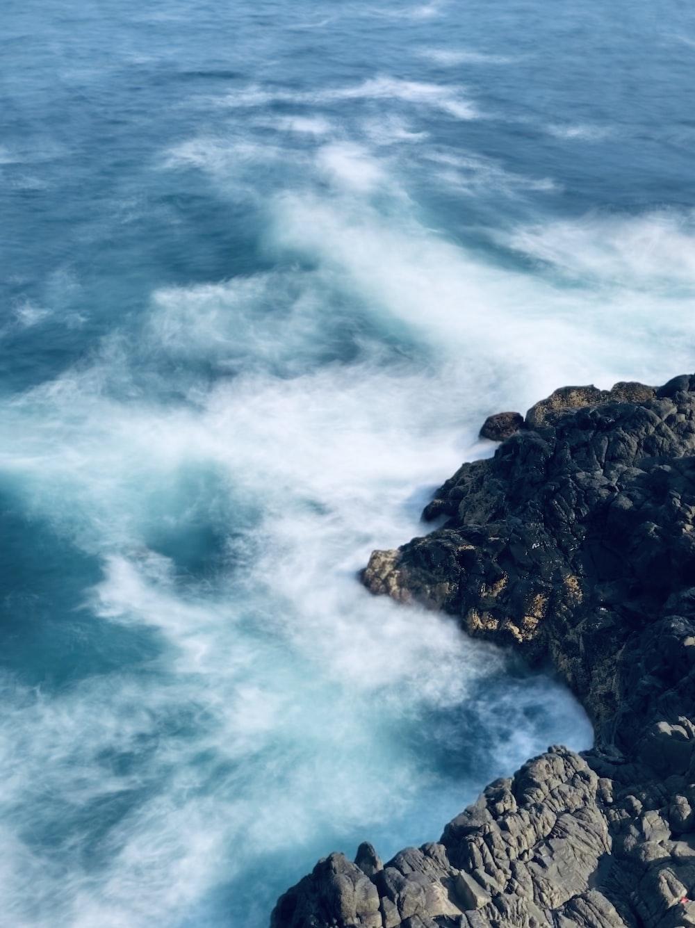 blue sea waves in black stones