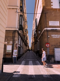 man walking near two brown concrete buildings