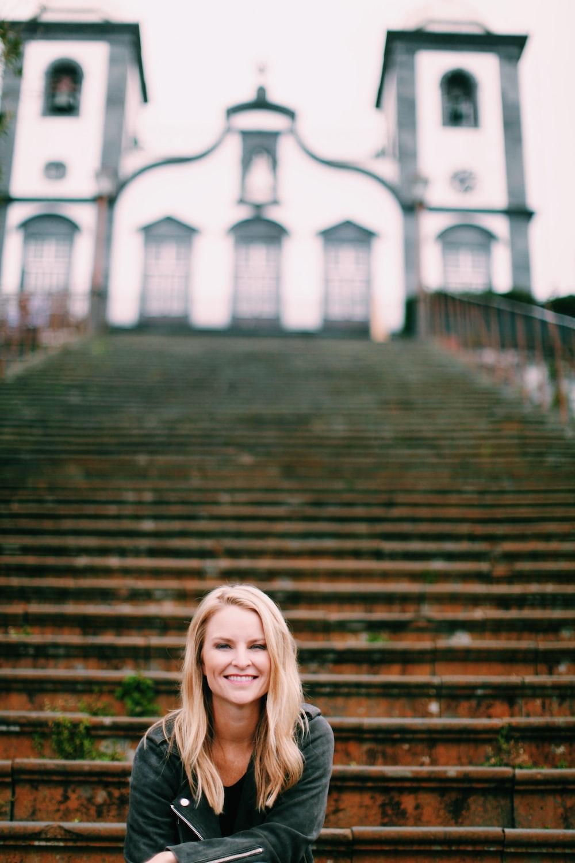 smiling woman sitting on stairway