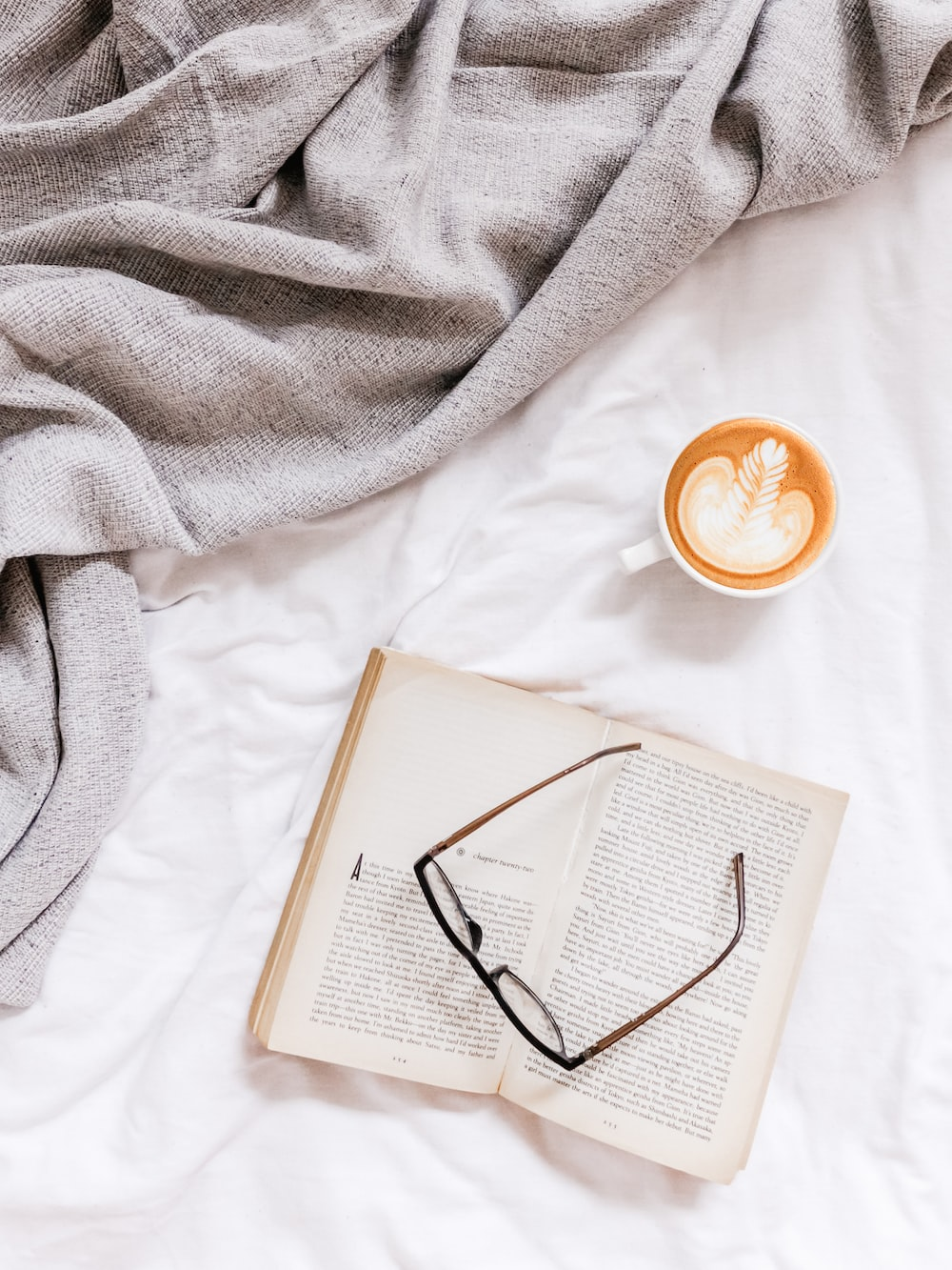 flat lay photography of eyeglasses on top of open book beside cup of coffee late