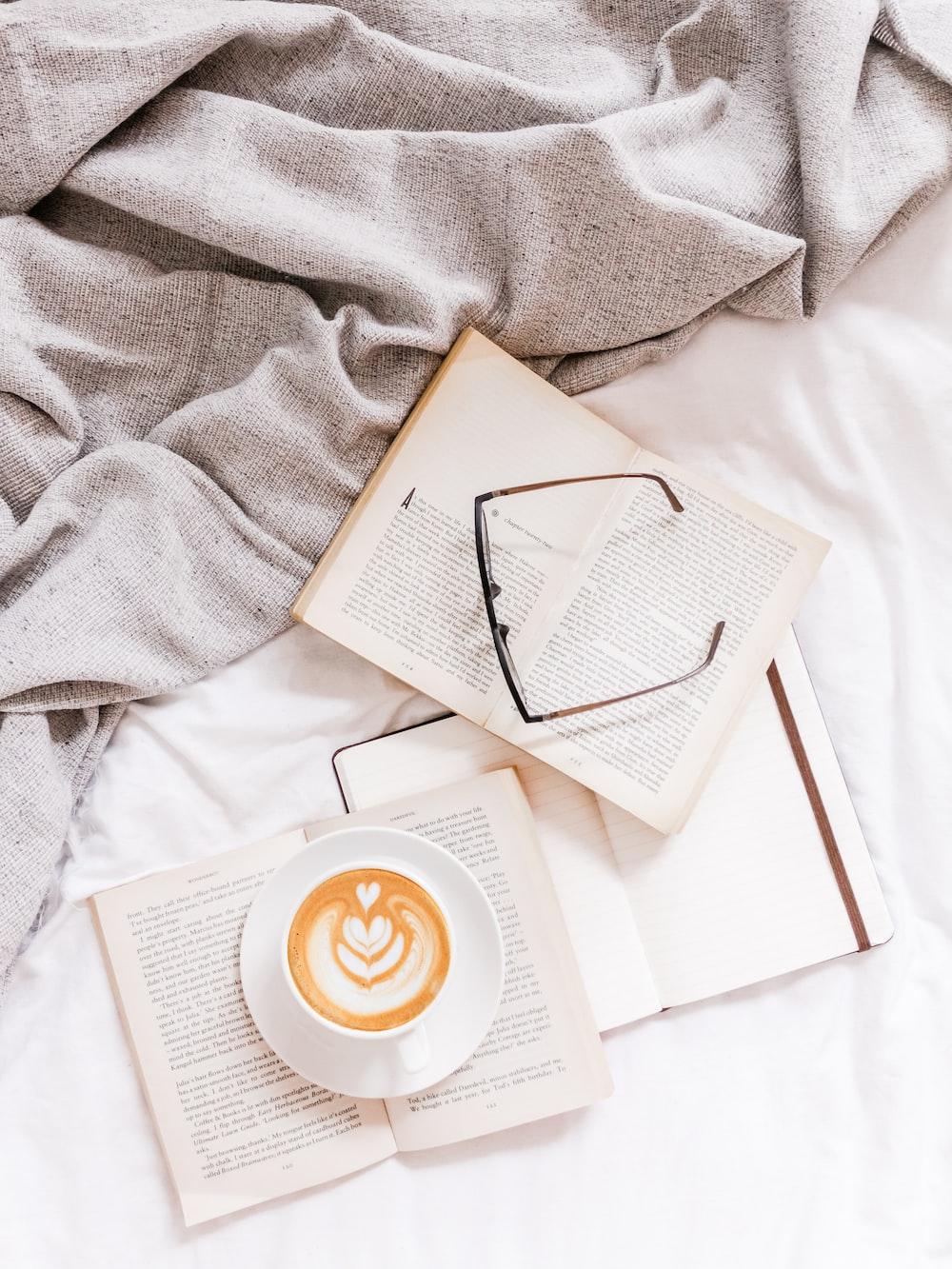 three opened books and eyeglasses on white textile