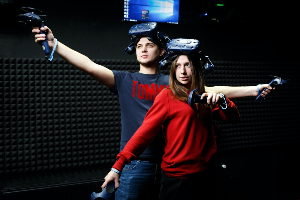 man and woman wearing black VR headsets