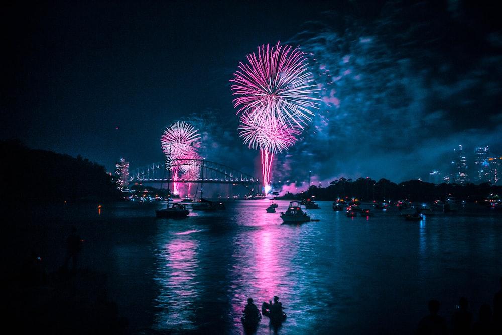 fireworks above long bridge at night-time