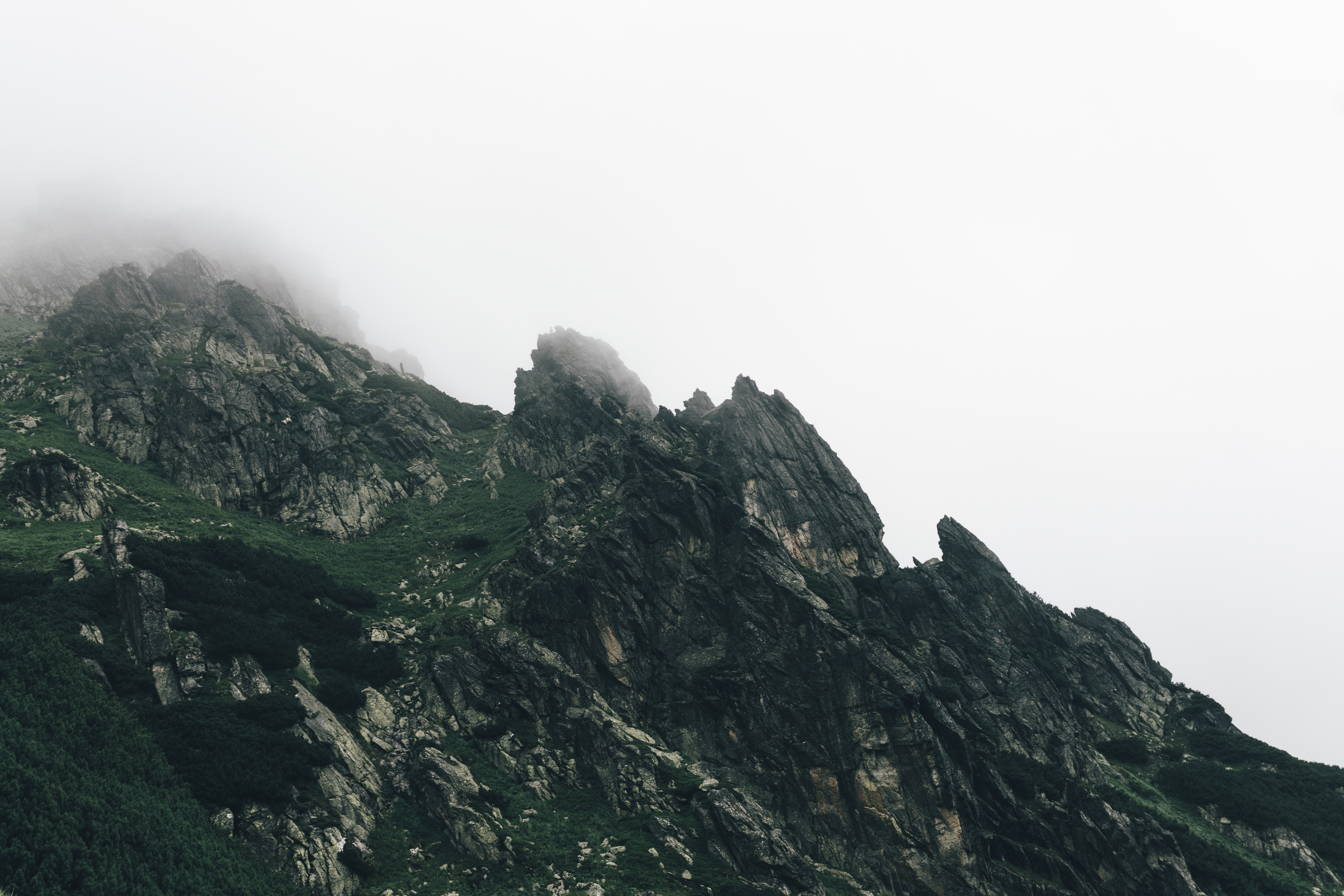 mountain covered in mist under cloudy sky