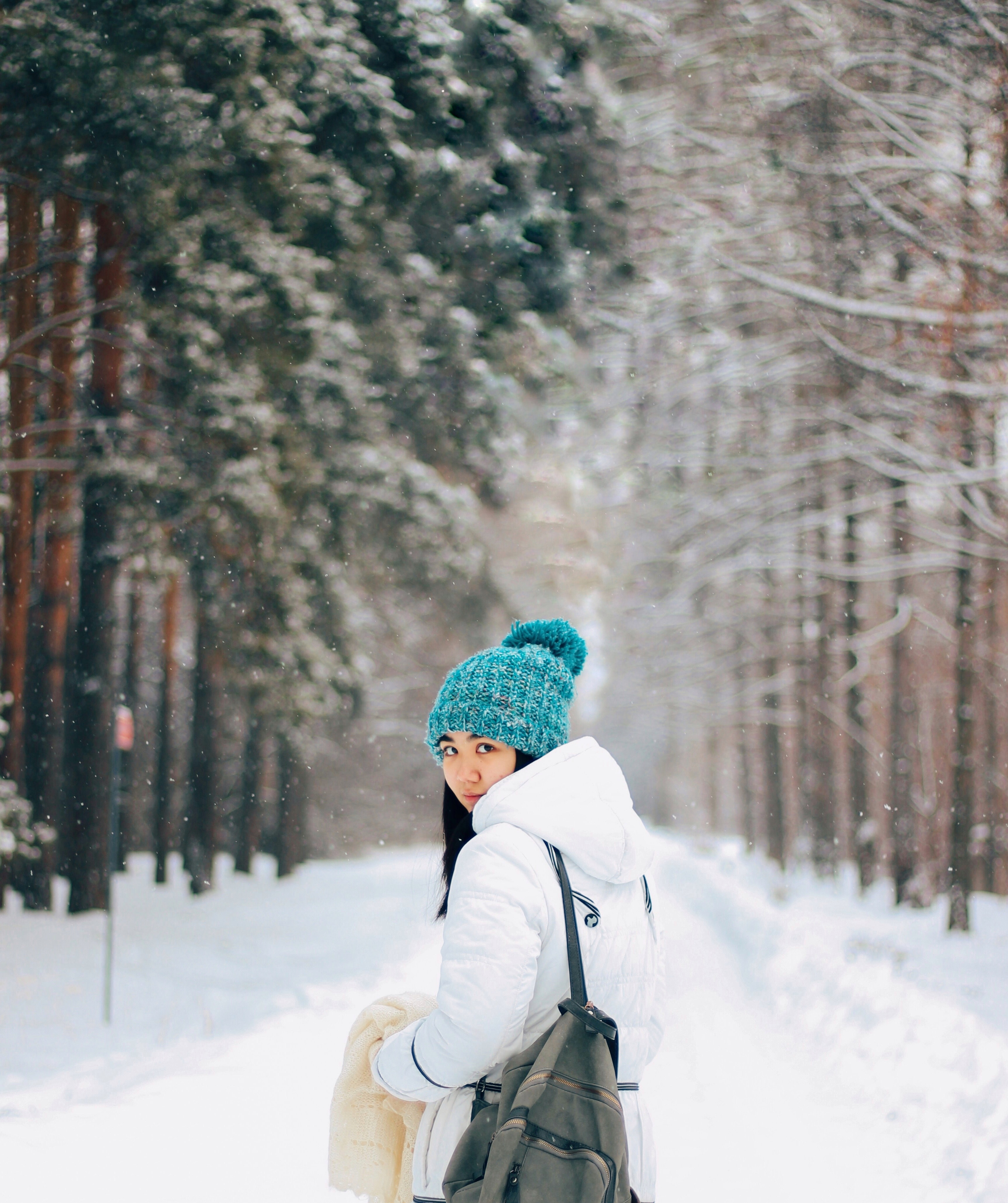 woman wearing white coat standing near snow-capped pathway near trees