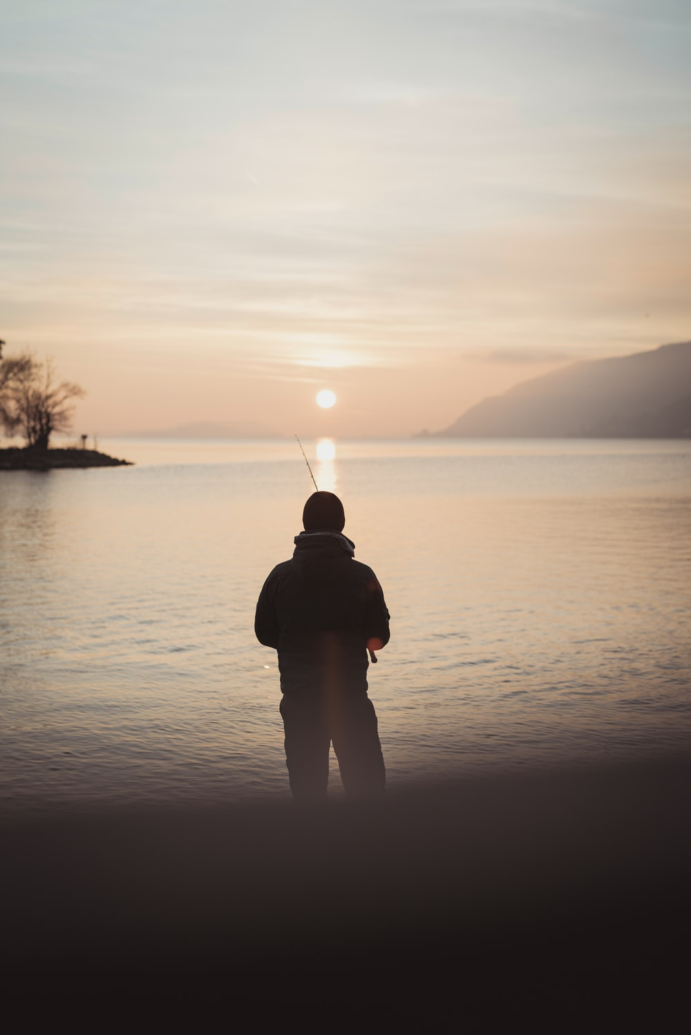 silhouette of person holding fishing rod across body of water