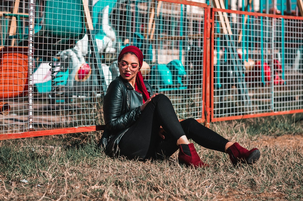 woman sits on green at the back of link fence