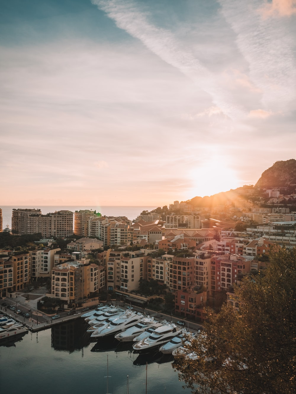 sun rising over hills near city by sea