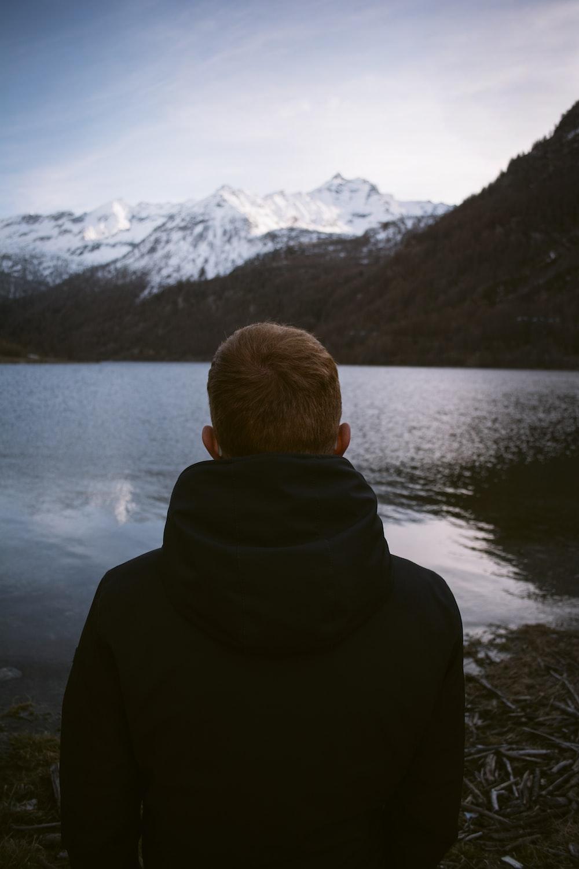 person wearing black jacket facing through body of water