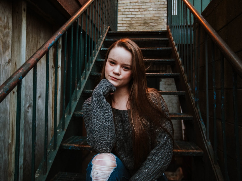 woman sitting on stairs during daytime