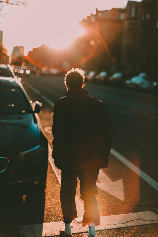 man standing beside black vehicle