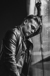 man with black leather jacket leaning on wall