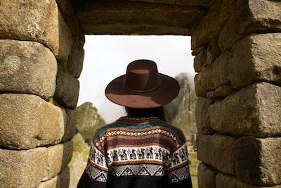 woman standing under brown rock formation peru zoom background