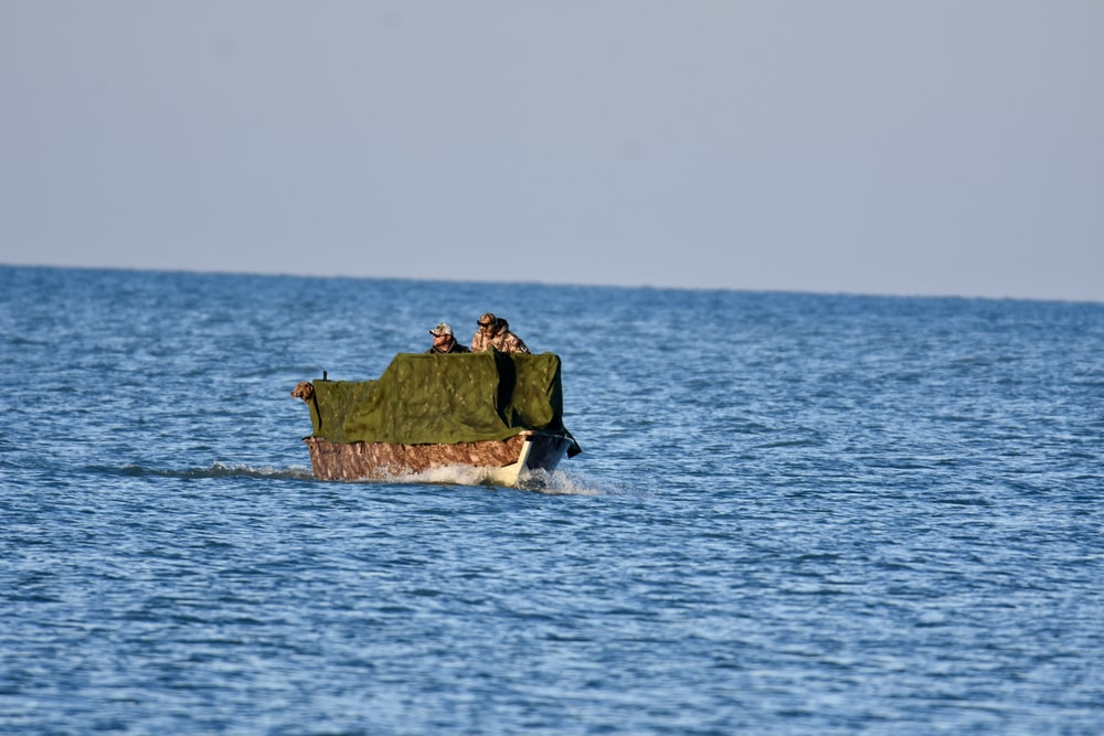 green and brown boat on body of water during daytime