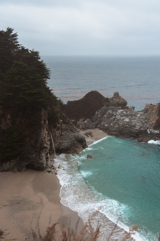 seashore near rock formation during daytime