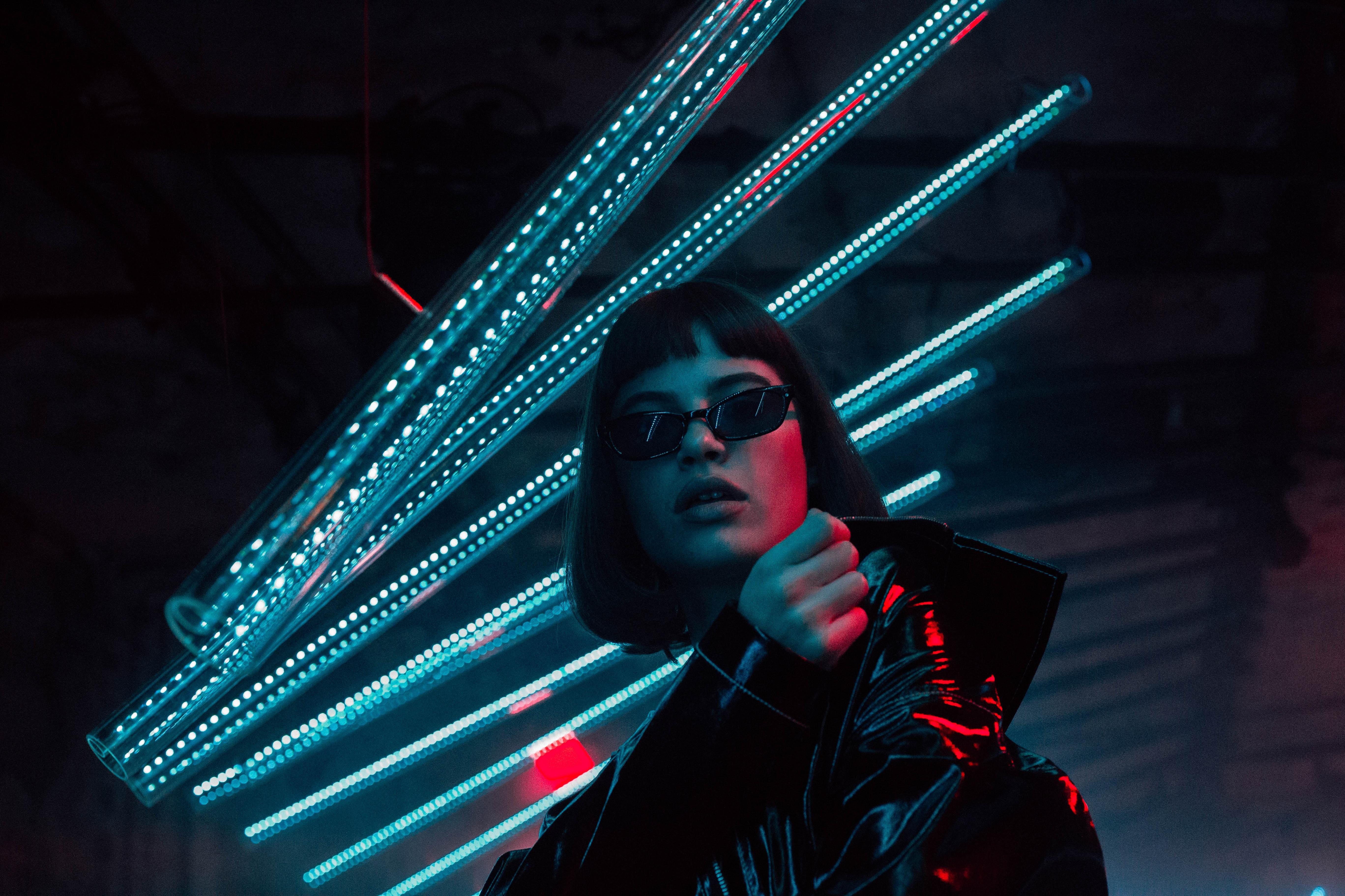 woman standing below blueneon lights