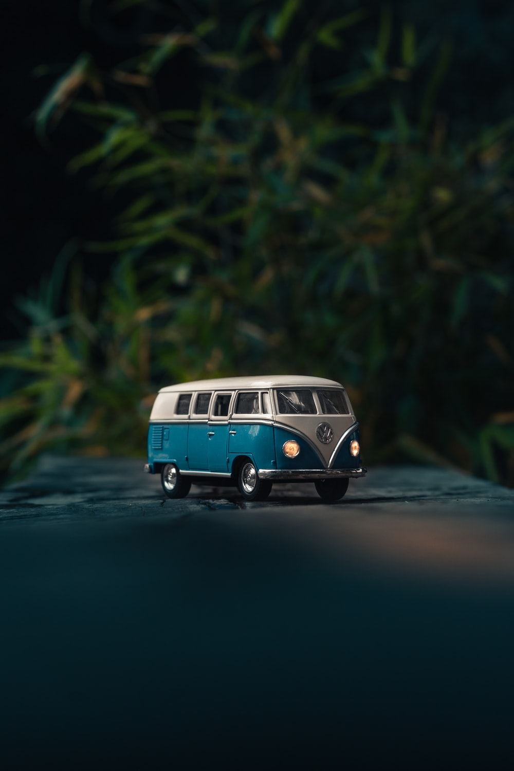 white and blue Volkswagen T1 van toy on gray surface