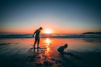 man standing on beach beside girl playing sand during sunset