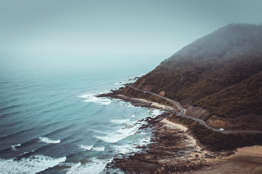 aerial photography of mountains beside road and sea