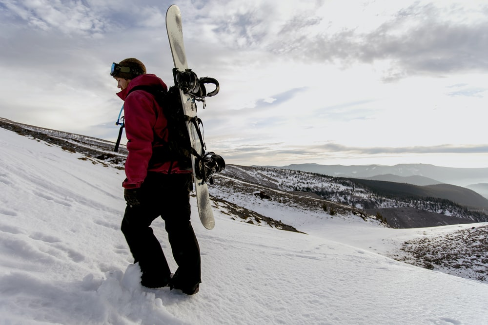 woman walking on snow carrying snowboard