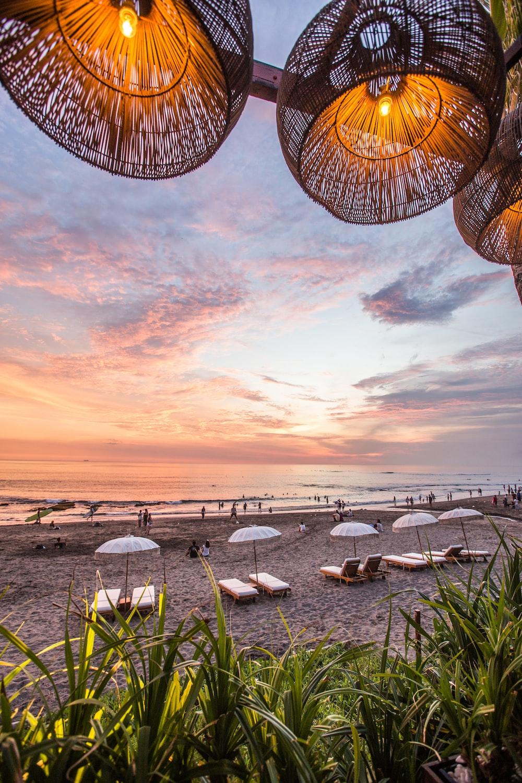 white parasol and lounge near seashores