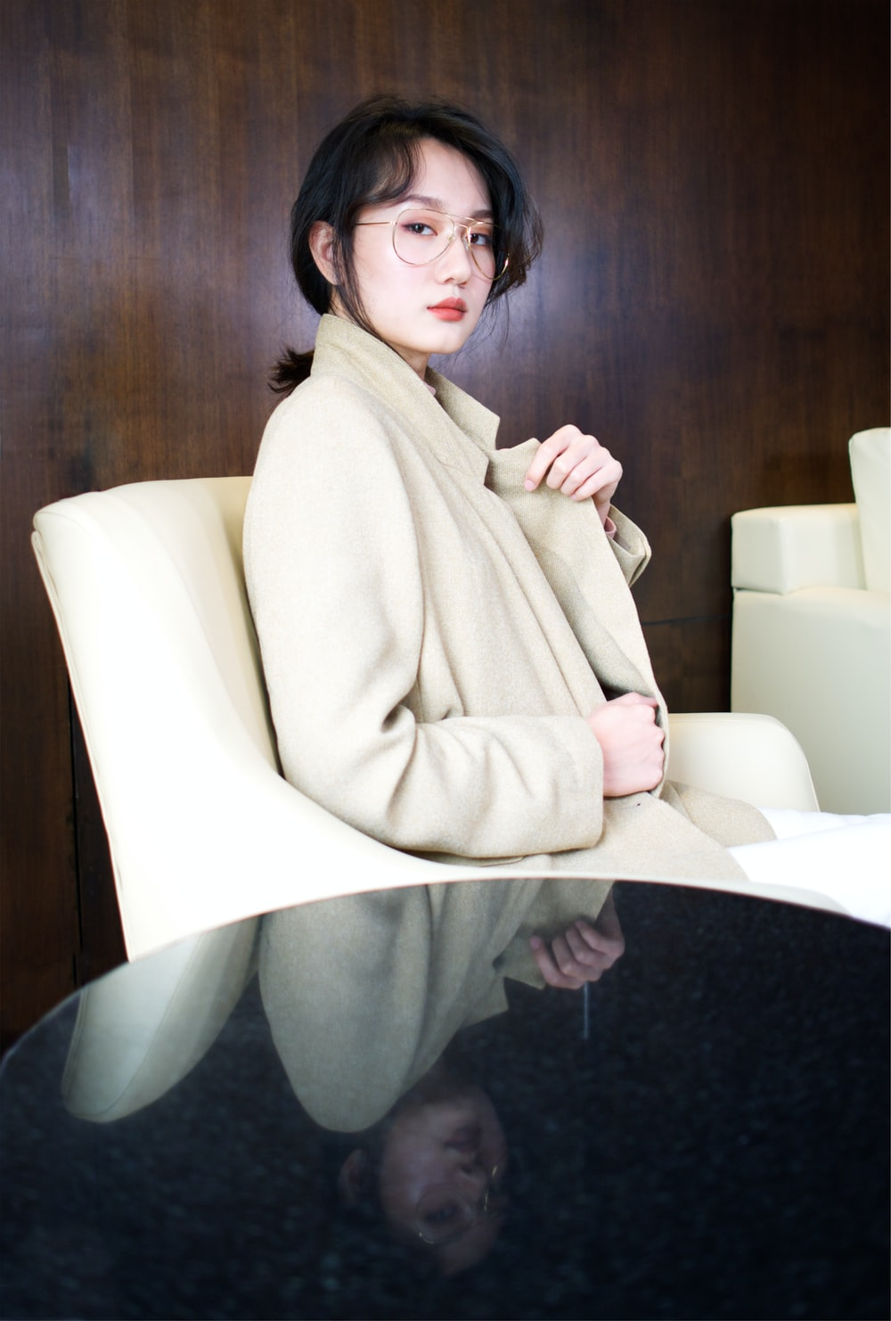selective focus photography of woman wearing brown coat sitting on sofa chair