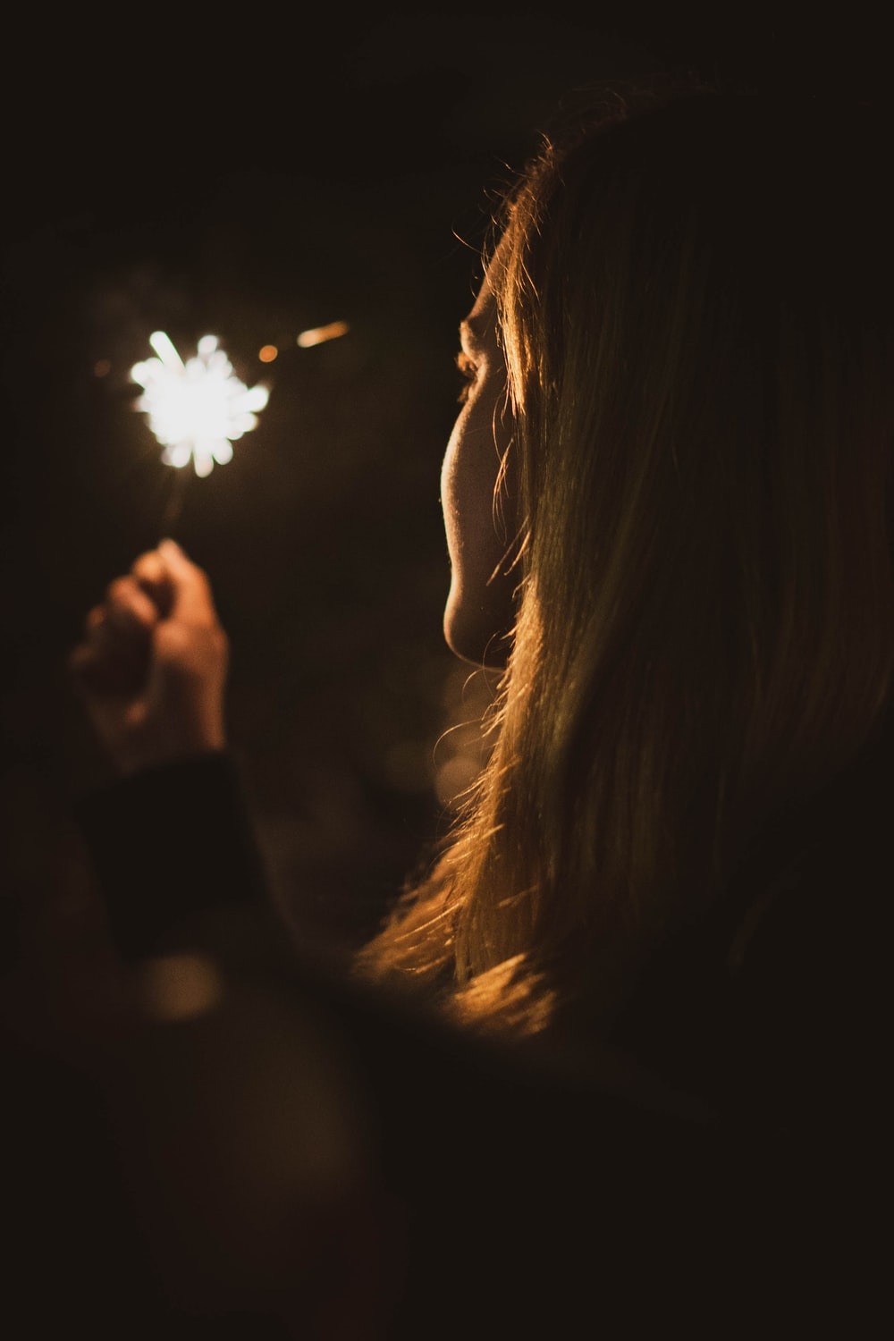 woman holding fireworks close-up photo