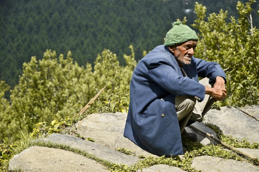 man wearing blue jacket across woods