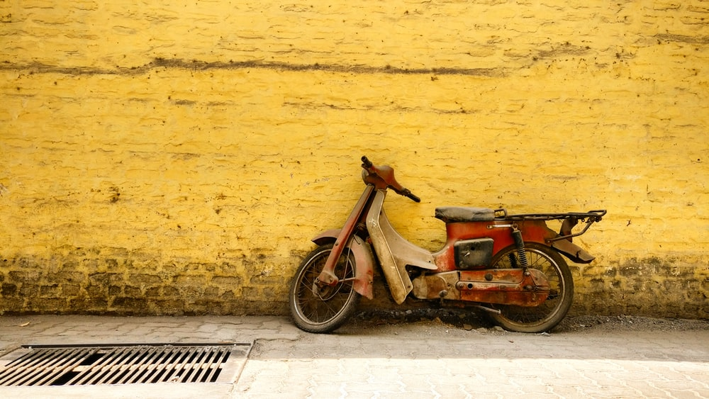 red underbone motorcycle parked on road