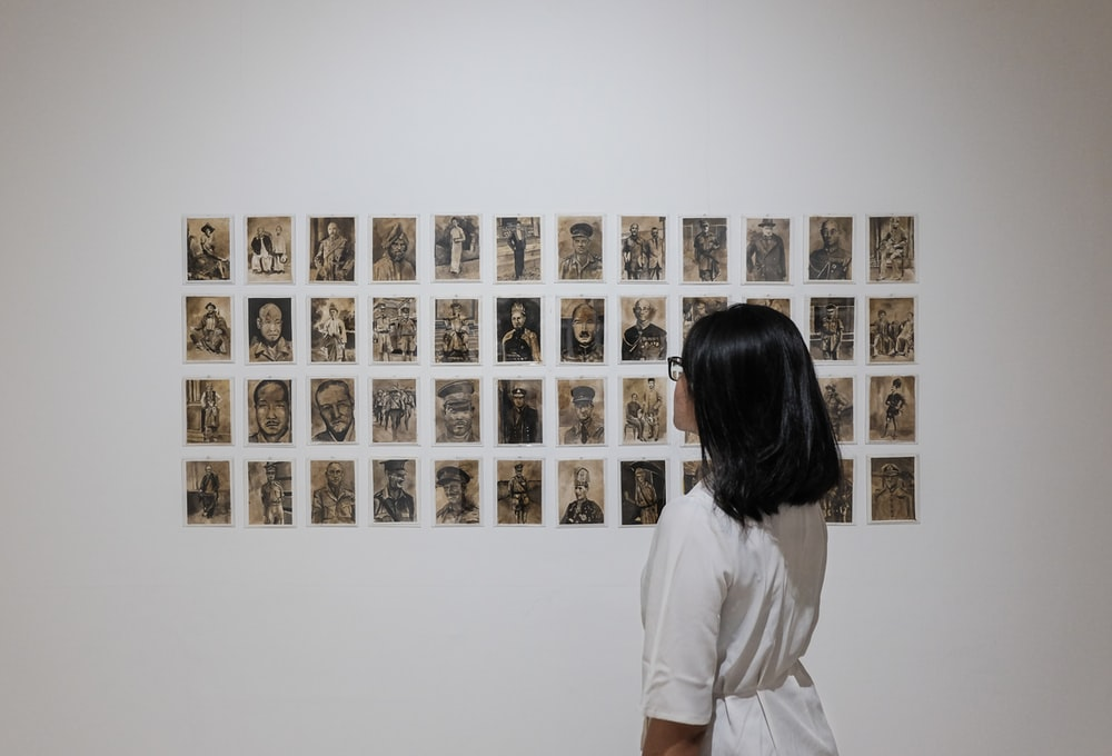 woman in white dress standing and looking at art of photos