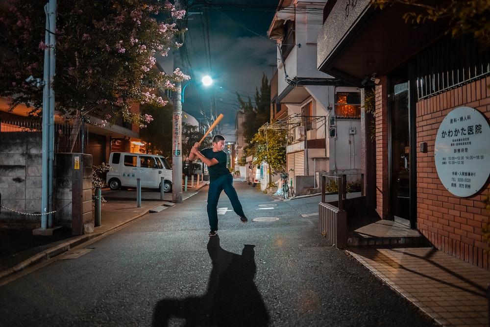 man in black shirt holding baseball bat at street during nighttime