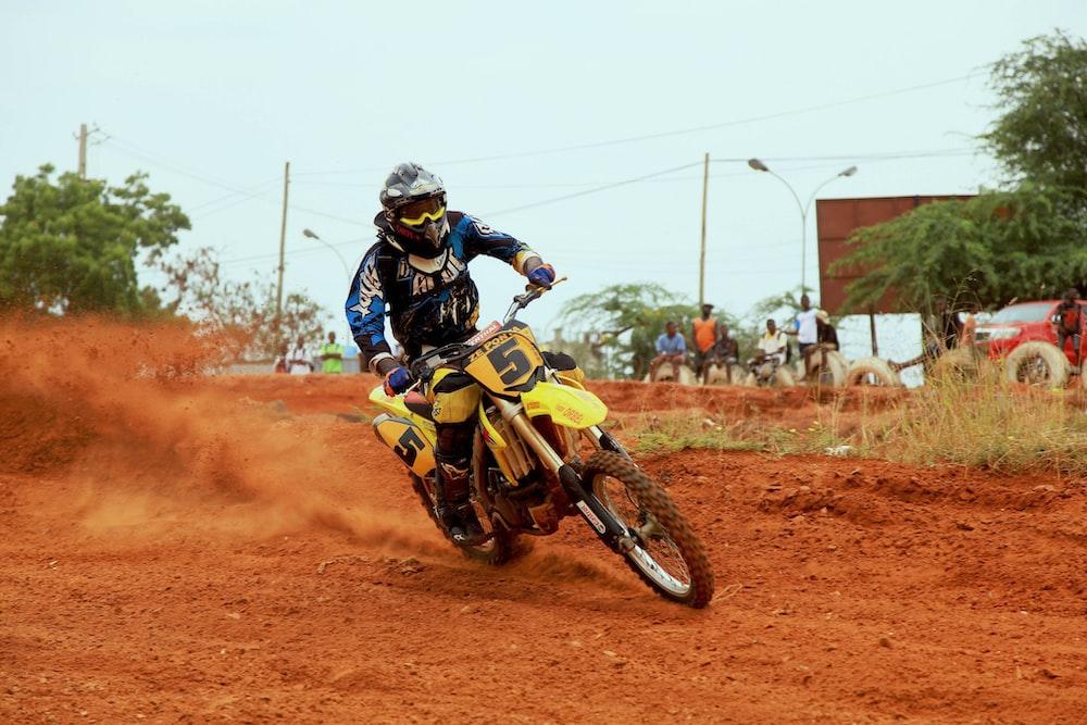 man riding on motocross dirtbike on field