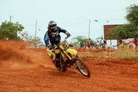 man riding on motocross dirtbike on field