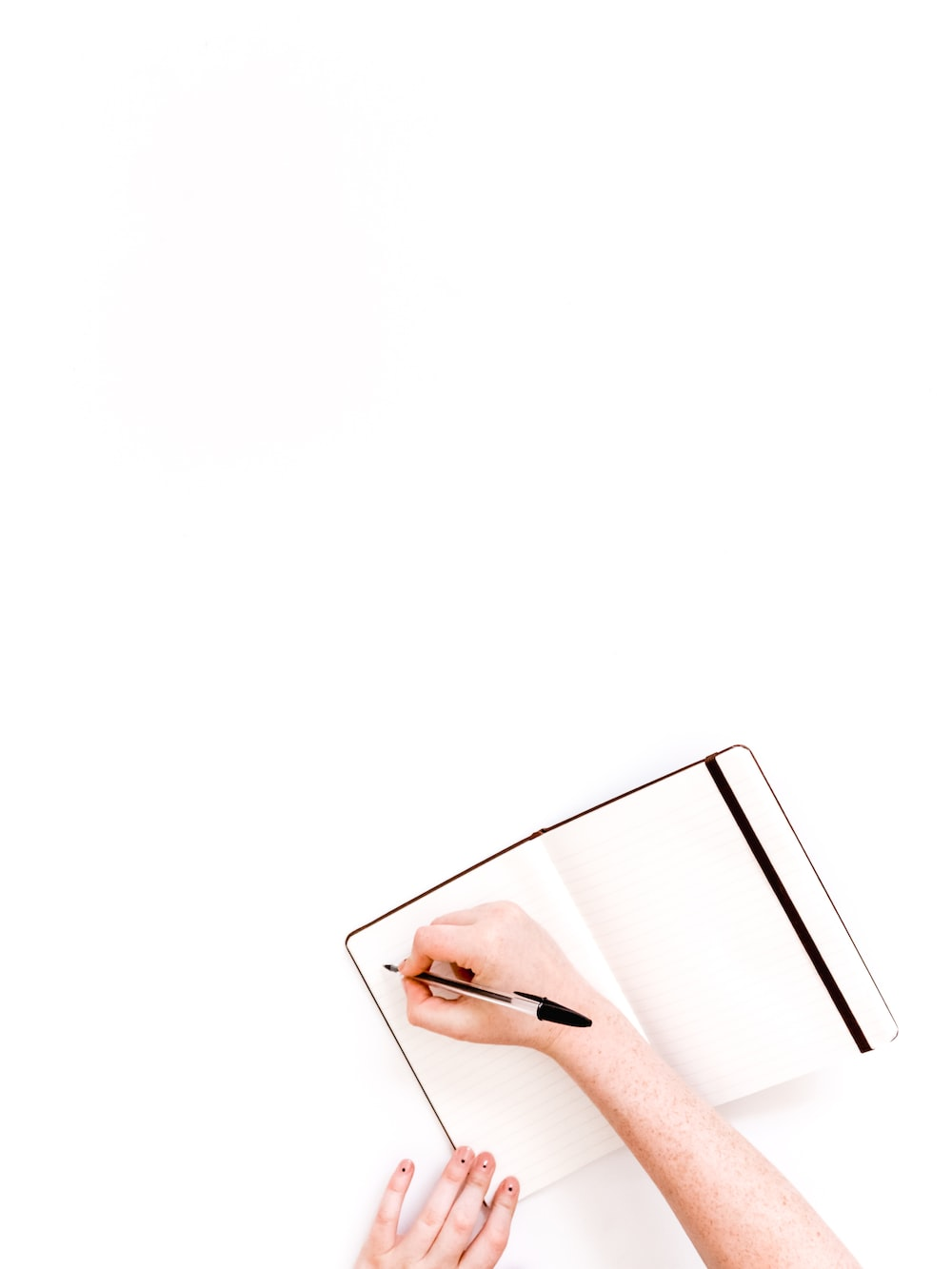 person holding ballpoint and writing on the book