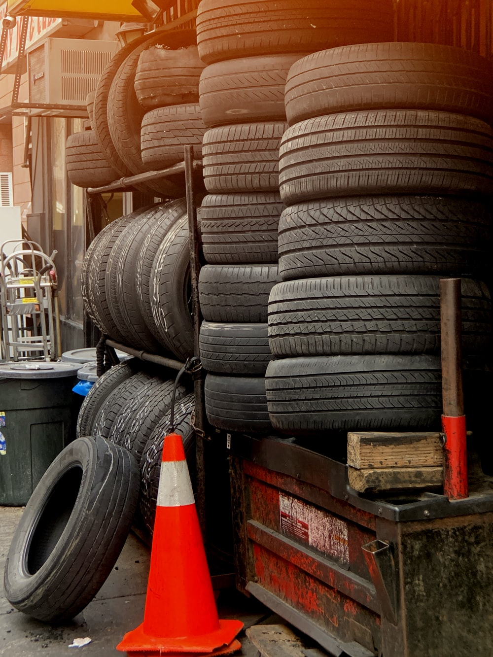 orange traffic cone near pile of vehicle tires