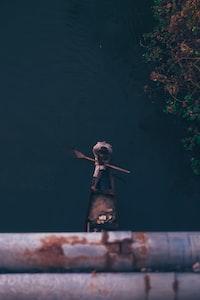 person sitting on boat holding oar