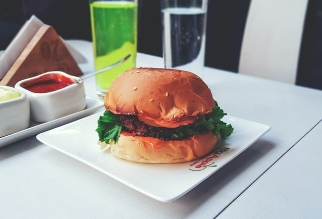 burger with green lettuce on white ceramic plate