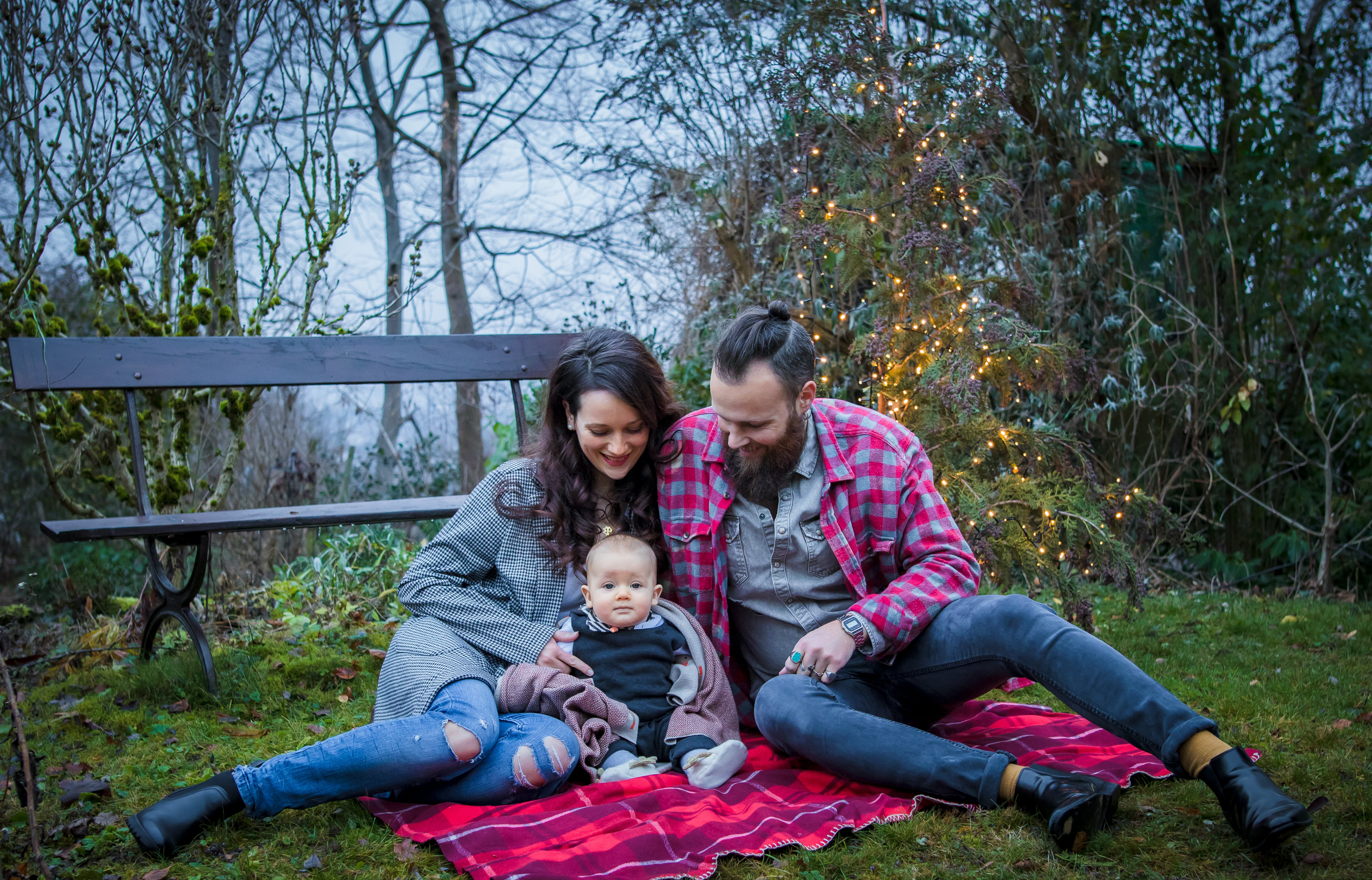 couple and baby sitting on picnic mat