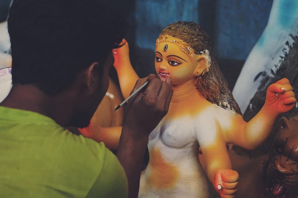 man making religious statuette