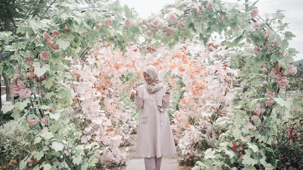 woman standing between heart framed flower garden \
