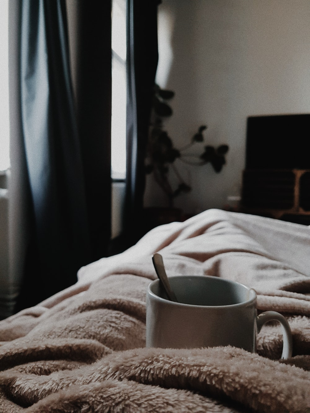 white ceramic mug on bed
