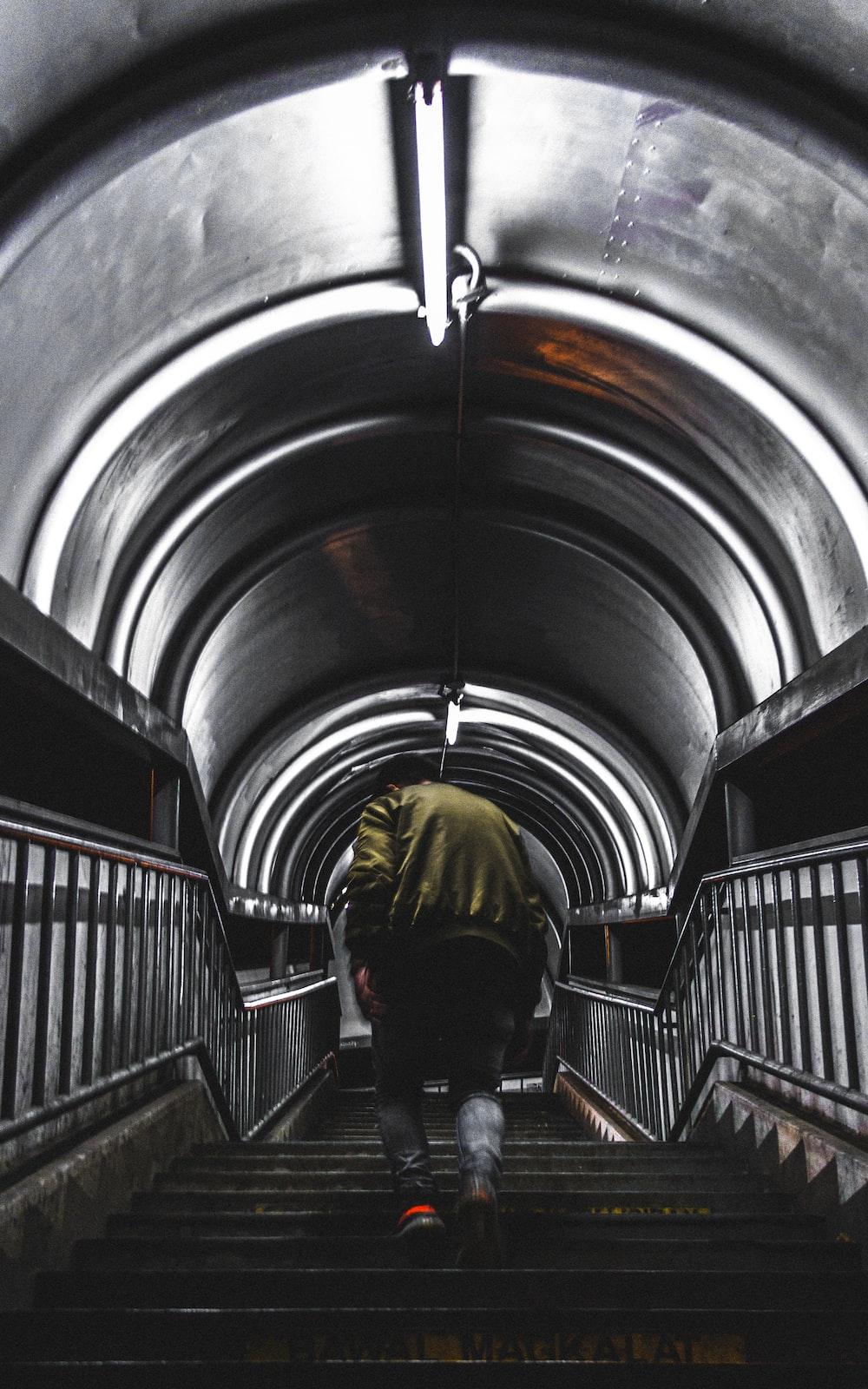 man in green jacket climbing stair under tunnel