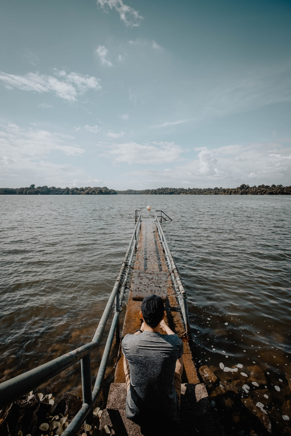 man sitting on small dock during daytime
