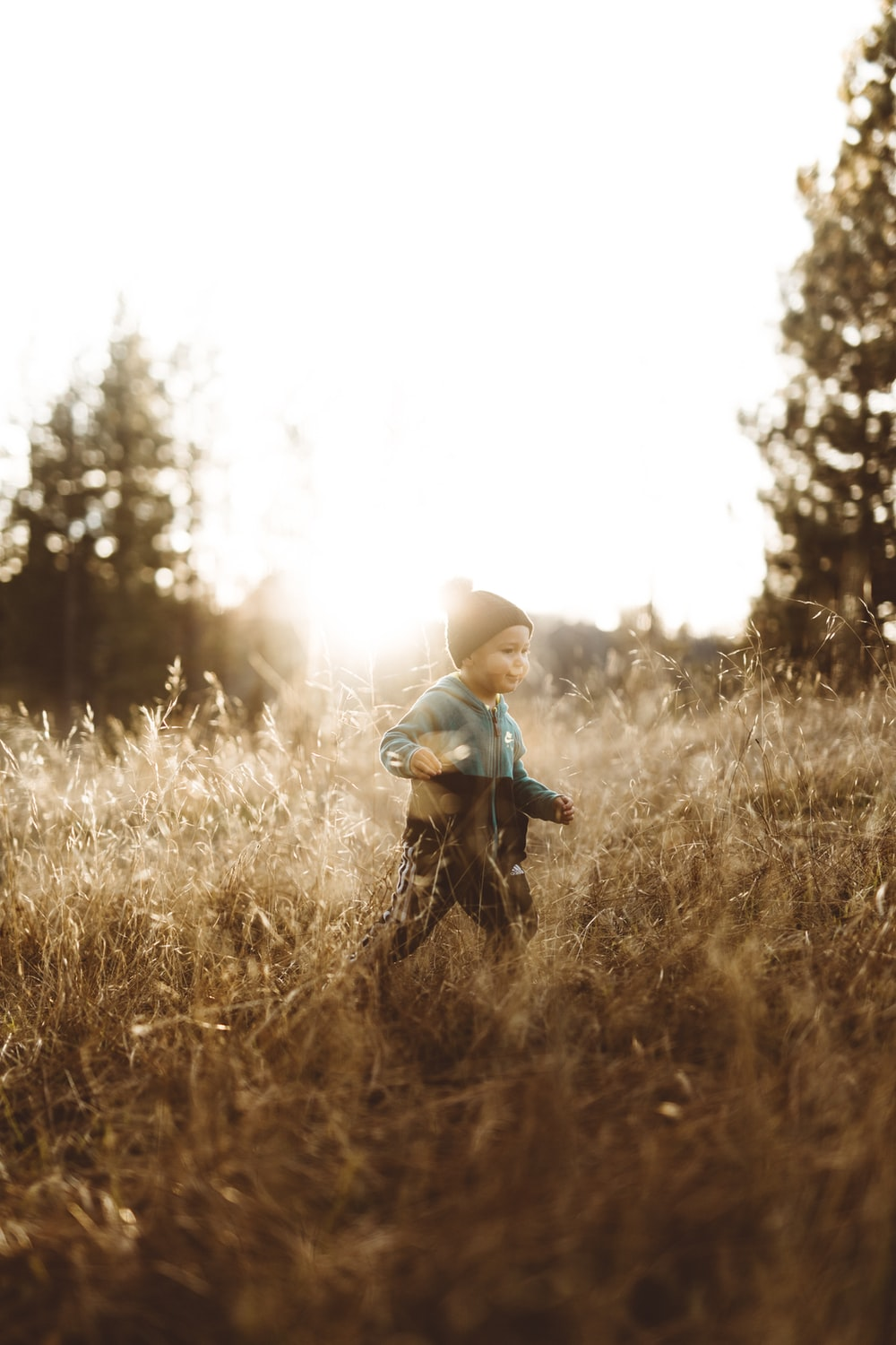 boy standing on brown grasses