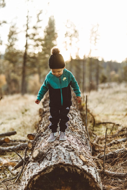 boy wearing jacket walking on tree trunk