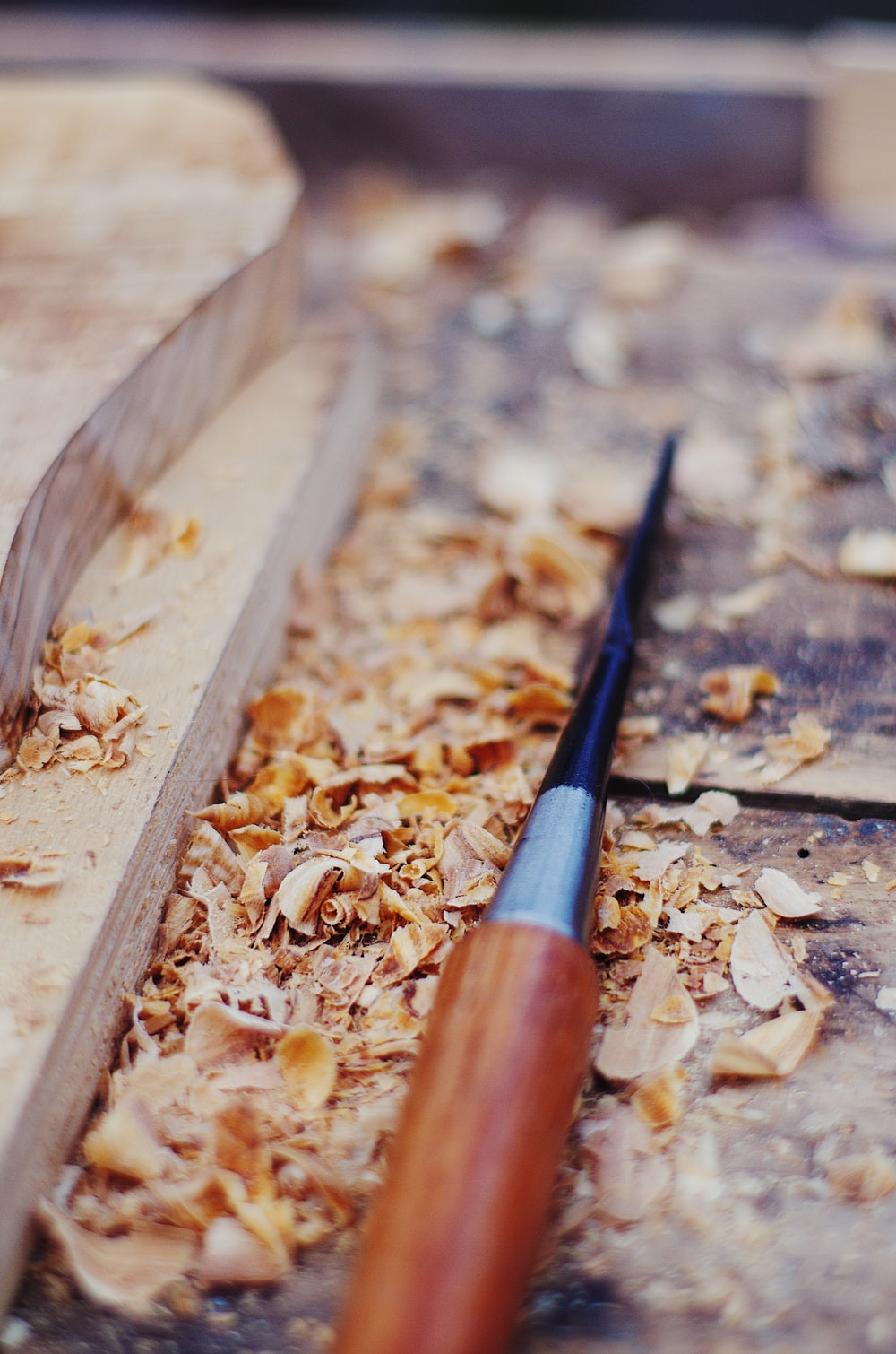 brown and black chisel on wood chips beside wood being carved