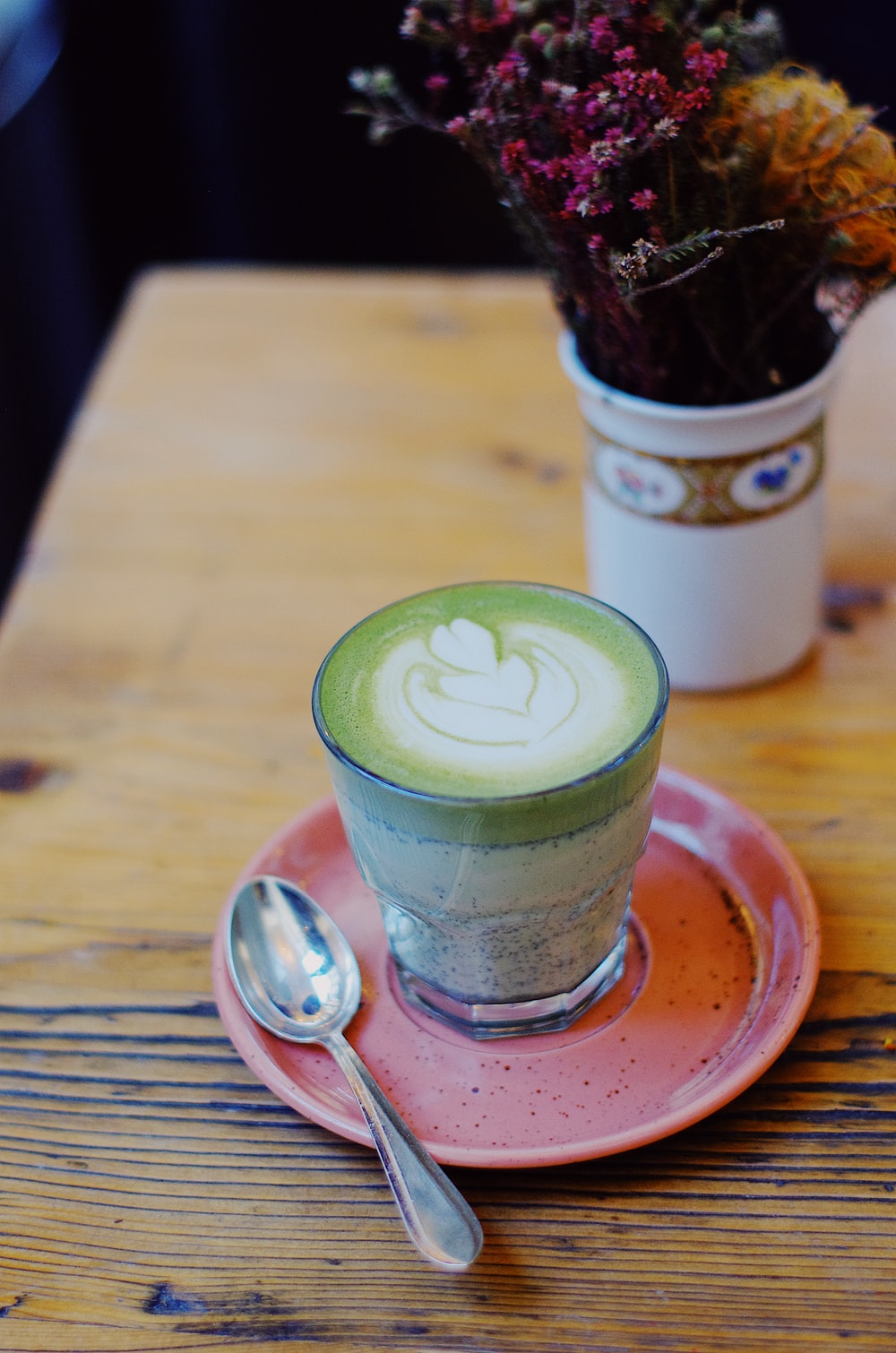 green and white beverage on saucer